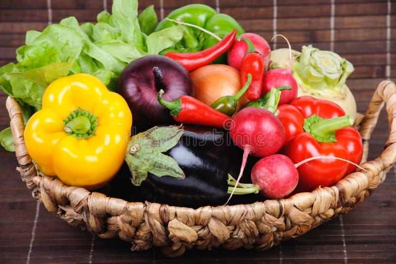 Verduras jugosas en una cesta, pimientas, cebollas, lechuga, rábano, fotos de archivo libres de regalías