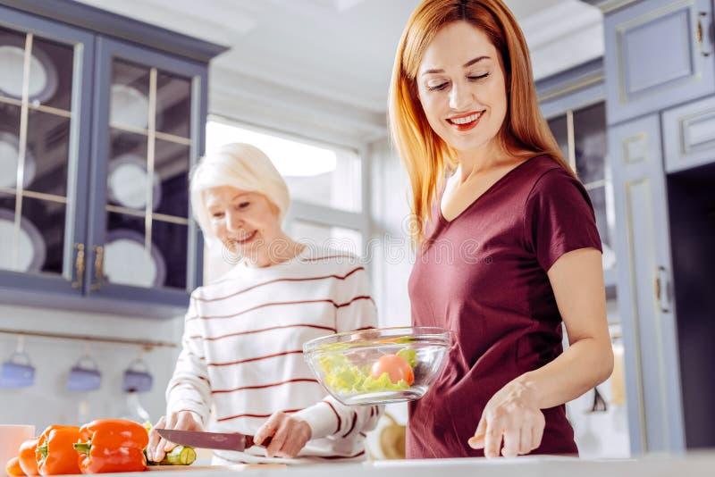 Verduras mayores del corte de la mujer mientras que cocina la ensalada con su hija foto de archivo libre de regalías