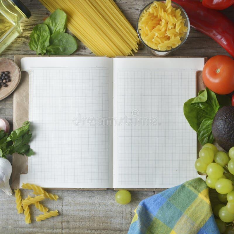 Verduras orgánicas frescas, fondo de madera y papel para las notas Abra el fondo del cuaderno y de las verduras frescas Concepto  imagen de archivo libre de regalías