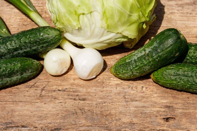 Verduras verdes frescas en la tabla de madera rústica Col, pepinos y cebolla en la tabla de madera Visión superior fotos de archivo libres de regalías