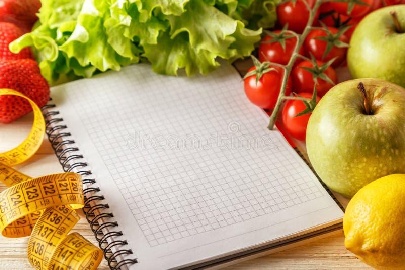 Verduras y frutas orgánicas frescas, cuaderno en blanco abierto y pluma imagenes de archivo