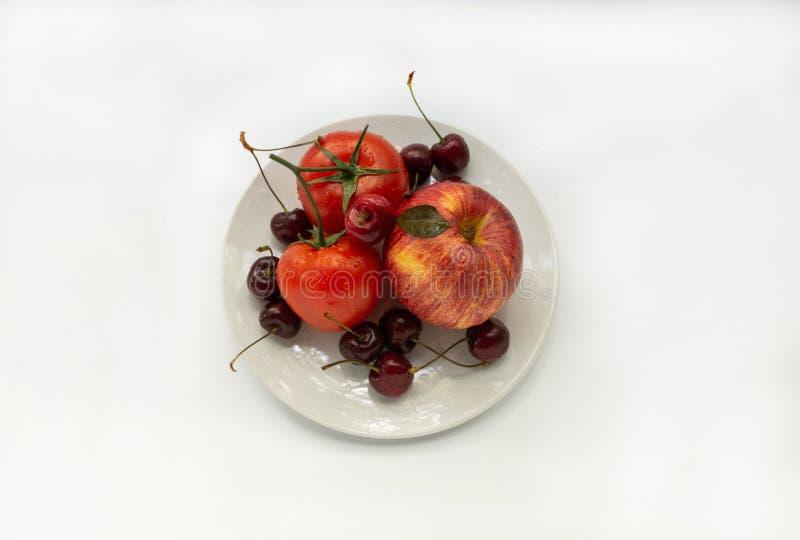 Verduras y frutas rojas en una placa blanca fotos de archivo