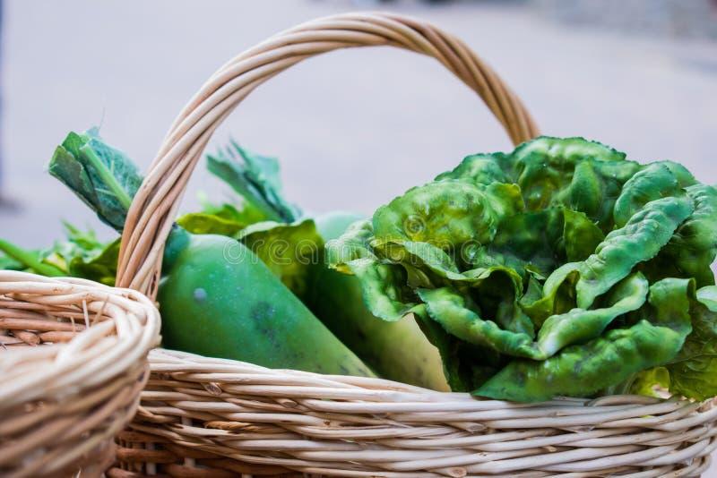 Verduras y hojas de ensalada jugosa, verde, col de China, rábano y apio en una cesta marrón de la vid después de cosechar en la a imágenes de archivo libres de regalías