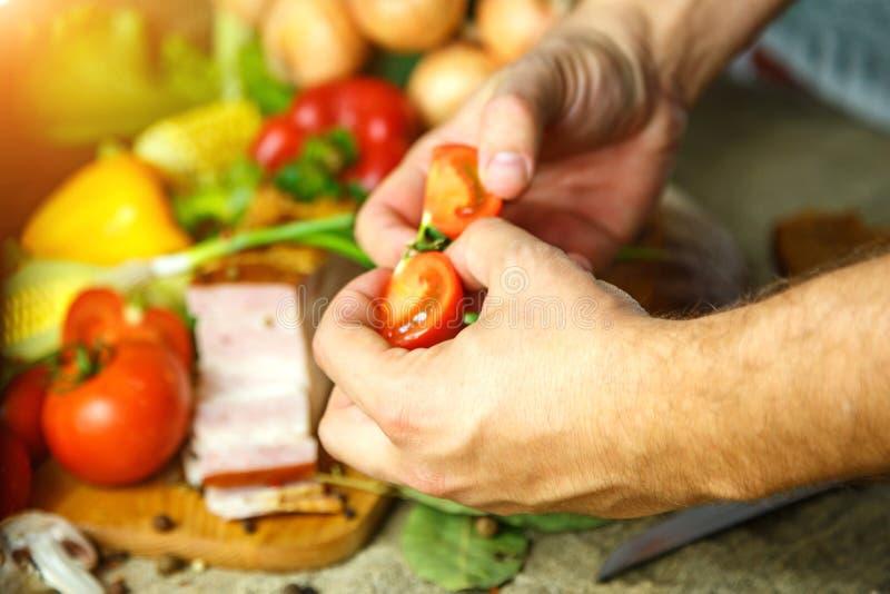 Verduras y manos que sostienen un tomate cortado imagenes de archivo