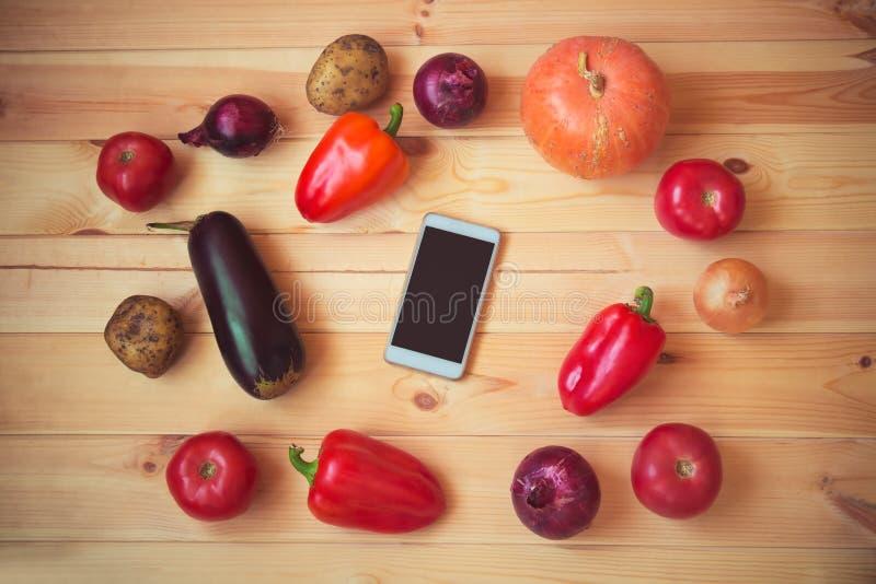 Verduras y smartphone org?nicos frescos en el centro en fondo de madera Visi?n superior, espacio de la copia imagen de archivo