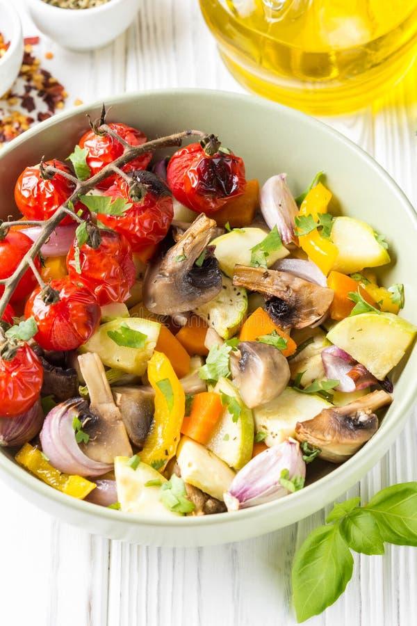 Verdure al forno con i funghi in una ciotola Zucchini, pomodori ciliegia su un ramo, cipolle rosse, peperoni dolci ed aglio squis fotografia stock libera da diritti