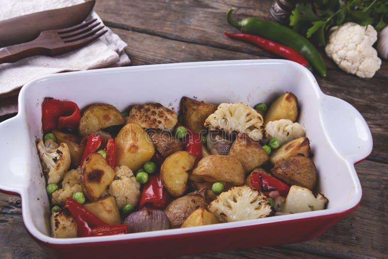 Verdure al forno nella fine rustica del piatto vegetariano del pepe del cavolfiore delle patate del forno su fotografia stock libera da diritti