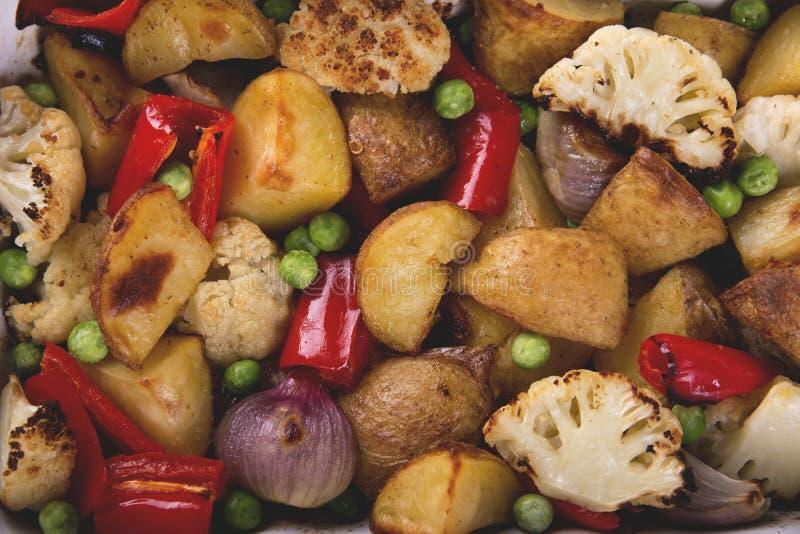 Verdure al forno nella fine rustica del piatto vegetariano del pepe del cavolfiore delle patate del forno su immagine stock