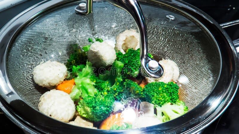 Verdure cotte a vapore sane in una pentola in pieno di acqua bollente e del vapore immagine stock