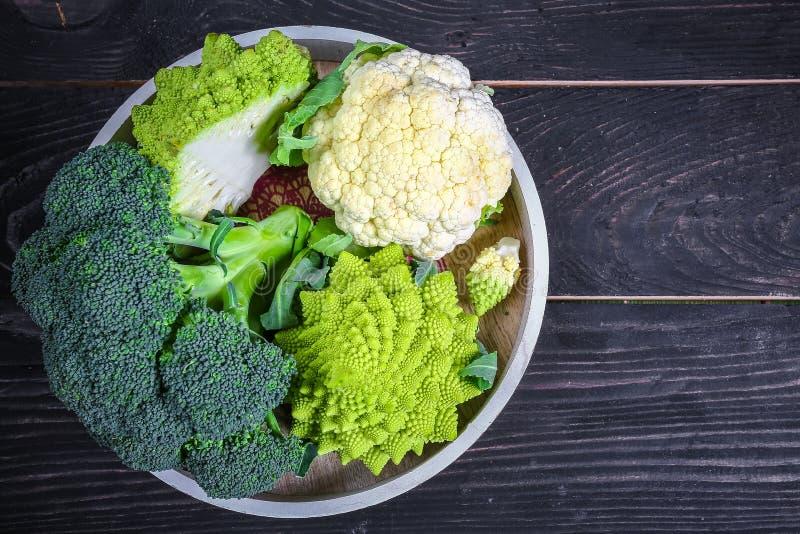 Verdure crocifere Romanesco, cavolfiore e broccoli su un vassoio rotondo su un fondo di legno Disposizione piana Vista superiore fotografia stock libera da diritti