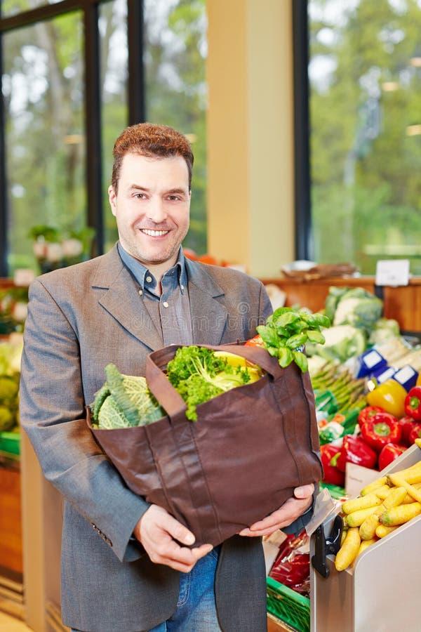Verdure d'acquisto sorridenti dell'uomo in supermercato fotografia stock libera da diritti