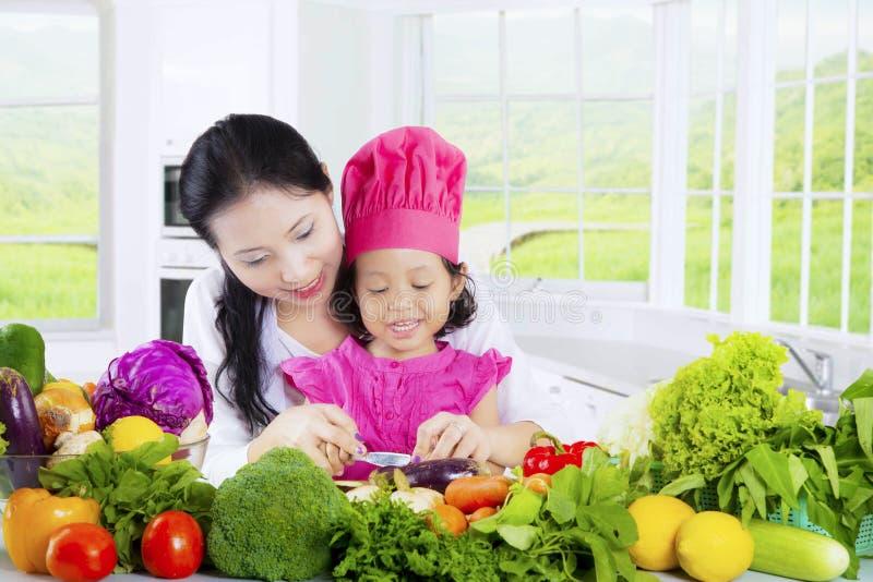 Verdure del taglio della madre e del bambino femminile fotografia stock libera da diritti
