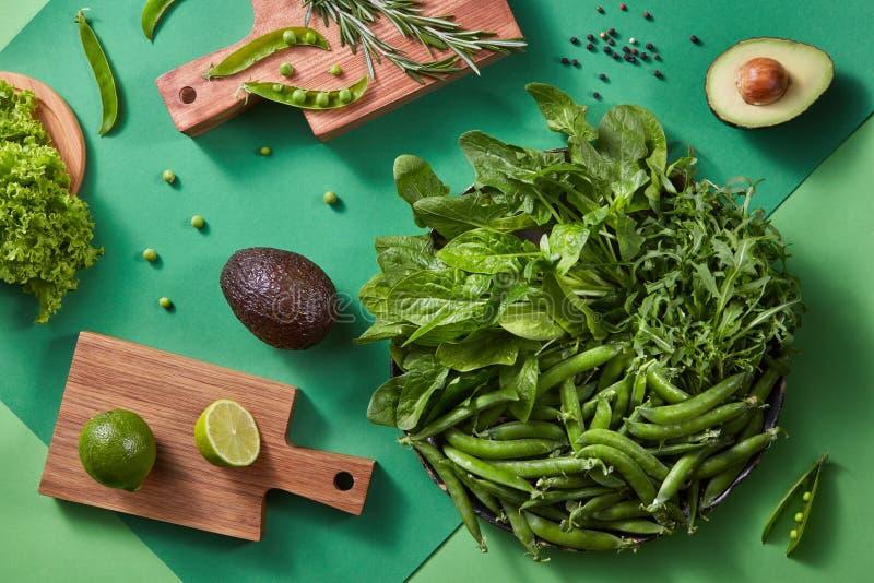 Verdure di Gren per insalata - la lattuga, i verdi, pisello attacca, rosmarini, l'avocado, calce su un tagliere di legno su un bi fotografia stock libera da diritti
