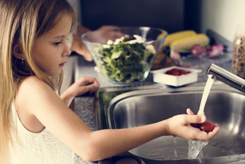 Verdure di lavaggio della ragazza nel lavandino di cucina fotografia stock libera da diritti