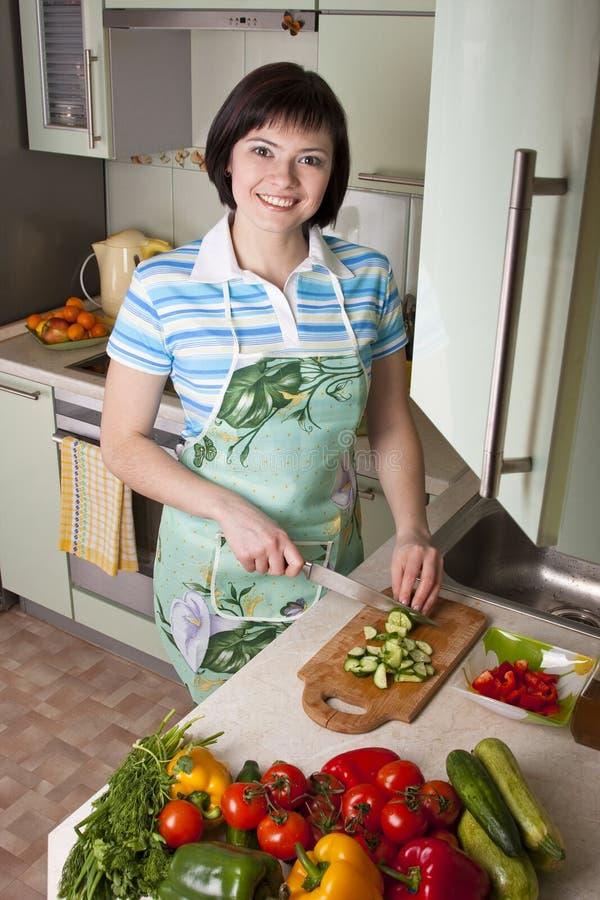 Verdure di taglio della donna nella cucina. immagini stock
