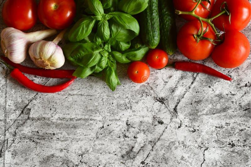 Verdure differenti su un bello fondo: pomodori maturi, cetrioli, aglio, basilico fragrante, peperoncini immagine stock libera da diritti