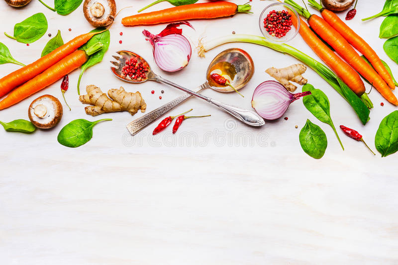 Verdure e cucchiai organici freschi su fondo di legno bianco, vista superiore, confine fotografia stock