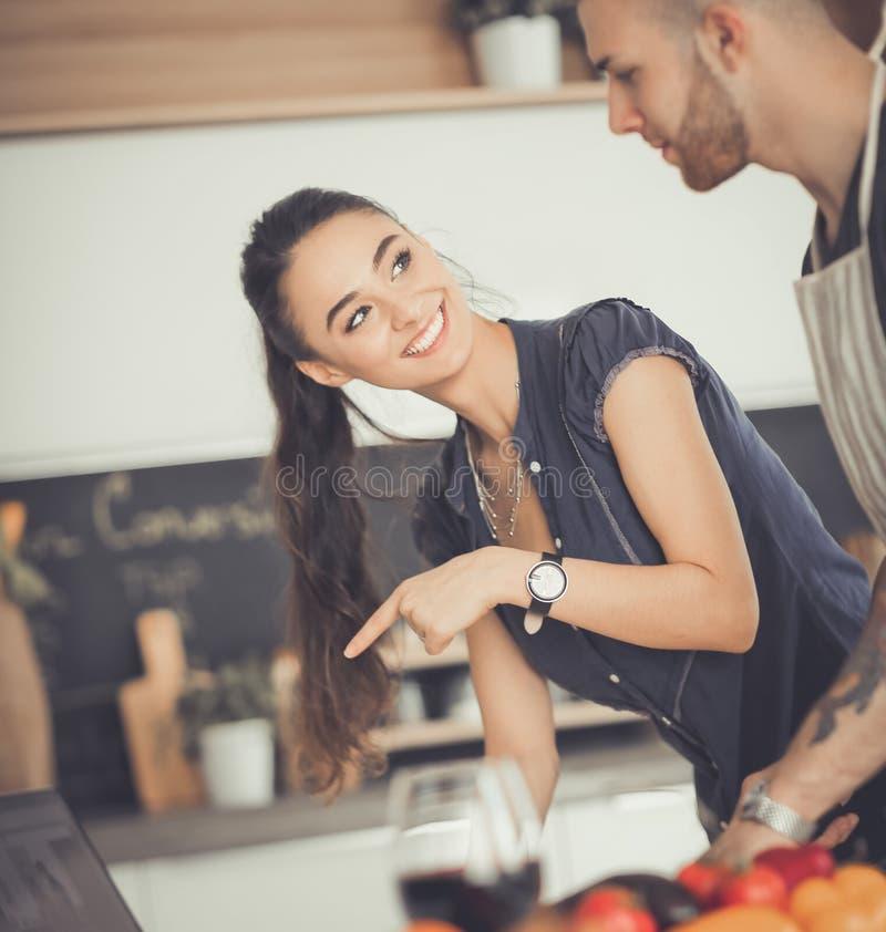 Verdure e donna di taglio del giovane che stanno con il computer portatile nella cucina immagini stock libere da diritti