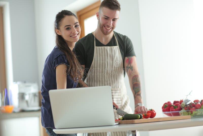 Verdure e donna di taglio del giovane che stanno con il computer portatile nella cucina immagini stock