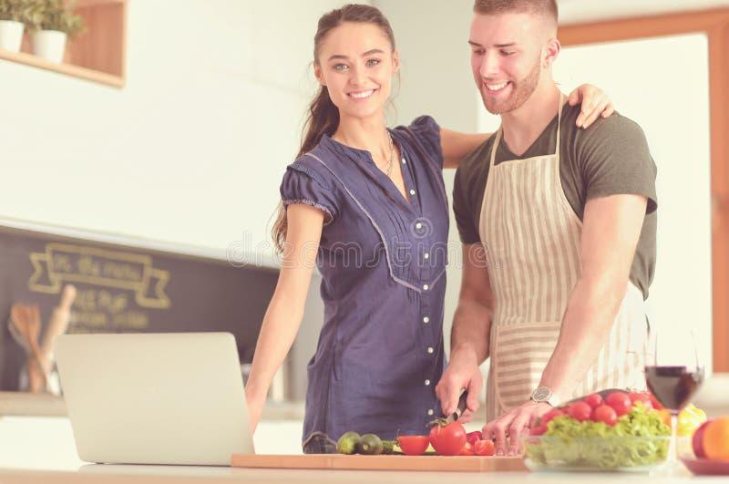 Verdure e donna di taglio del giovane che stanno con il computer portatile nella cucina fotografia stock libera da diritti