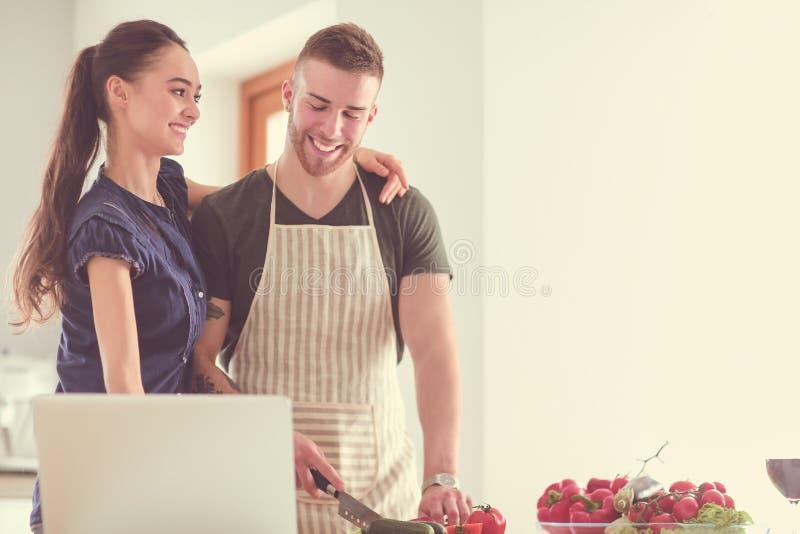 Verdure e donna di taglio del giovane che stanno con il computer portatile nella cucina fotografie stock