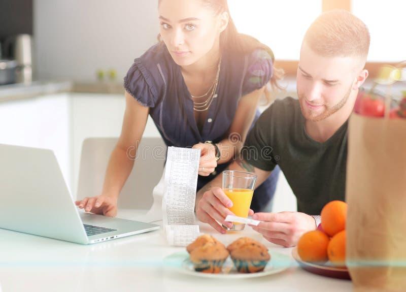 Verdure e donna di taglio del giovane che stanno con il computer portatile nella cucina fotografie stock libere da diritti