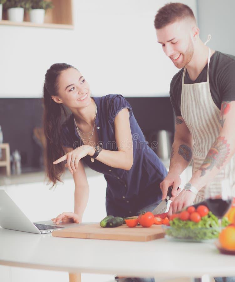 Verdure e donna di taglio del giovane che stanno con il computer portatile nella cucina fotografia stock