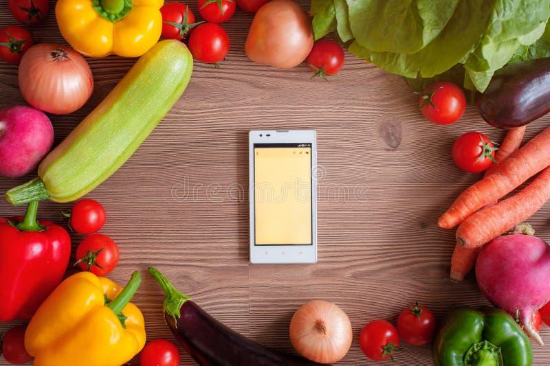 Verdure e smartphone nel centro su fondo di legno immagini stock