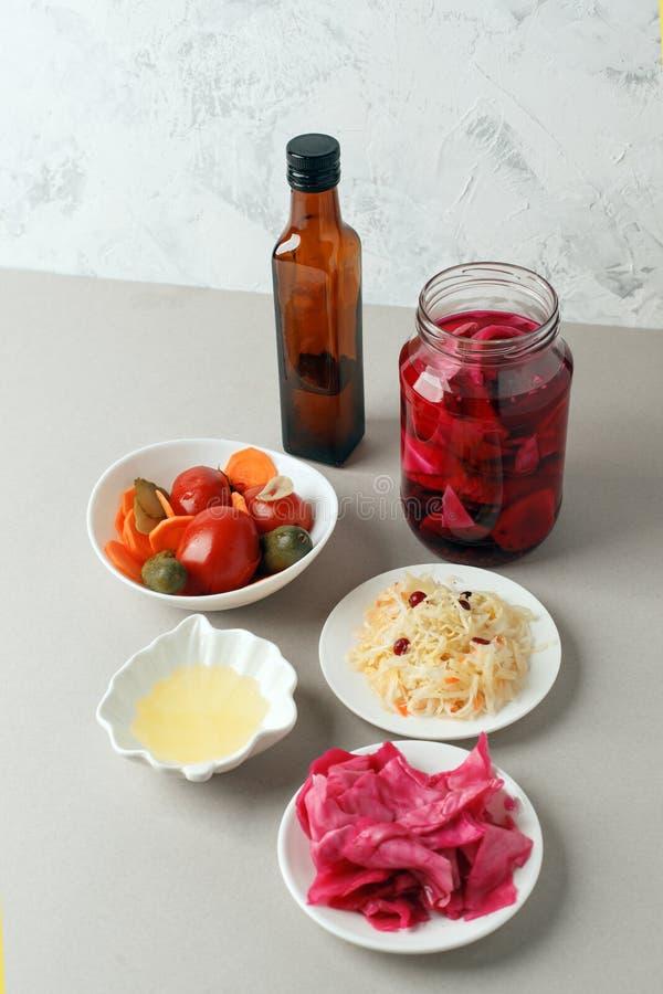 Verdure fermentate sul piatto su fondo grigio: crauti, cavolo marinato con barbabietola, cetrioli marinati, carote e immagine stock