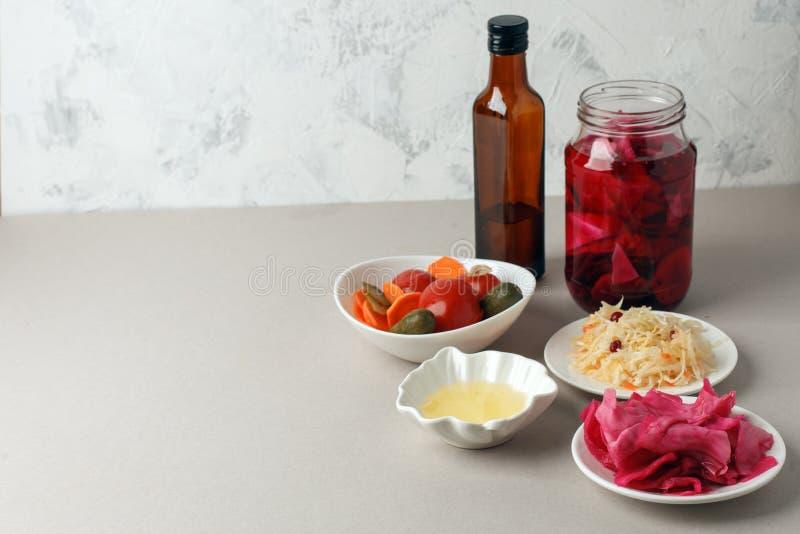 Verdure fermentate sul piatto su fondo grigio: crauti, cavolo marinato con barbabietola, cetrioli marinati, carote e immagini stock libere da diritti