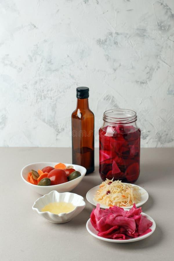 Verdure fermentate sul piatto su fondo grigio: crauti, cavolo marinato con barbabietola, cetrioli marinati, carote e fotografia stock