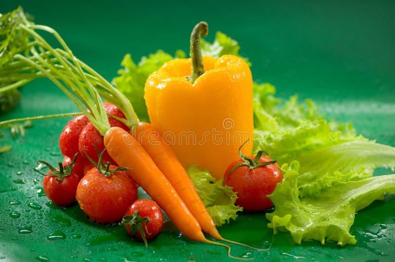 Verdure - lavi le carote con le cime, i peperoni gialli, i pomodori, lattuga fotografia stock