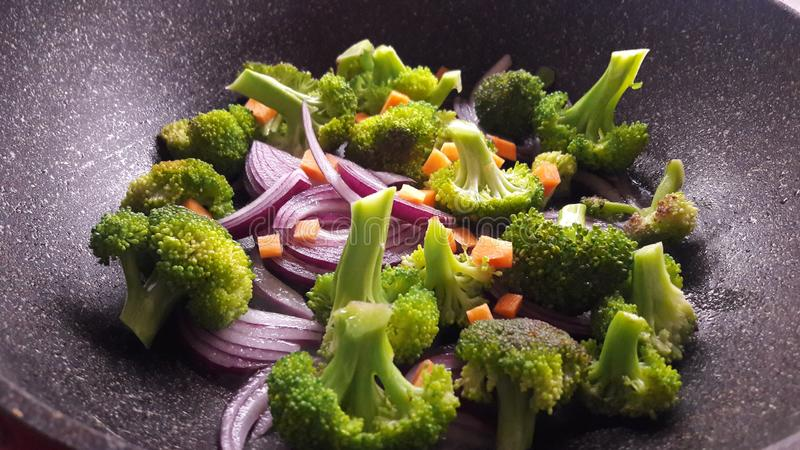 Verdure luminose fresche cucinate sul wok, broccoli, cipolle, carote immagini stock libere da diritti