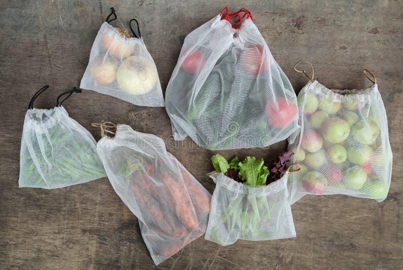 Verdure organiche fresche, frutta e verdi nelle borse riciclate riutilizzabili della maglia sulla tavola di legno Concetto residu fotografia stock libera da diritti