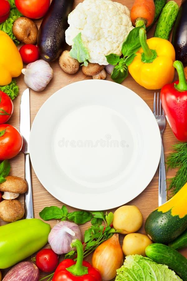 Verdure organiche intorno al piatto bianco con il coltello e la forcella fotografie stock libere da diritti