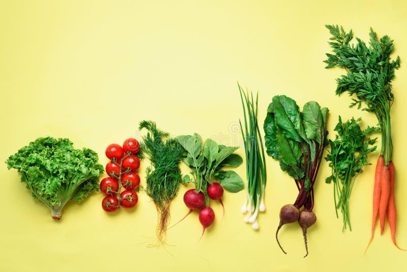 Verdure organiche su fondo giallo con lo spazio della copia Punto di vista superiore della carota, barbabietola, pepe, ravanello, fotografia stock