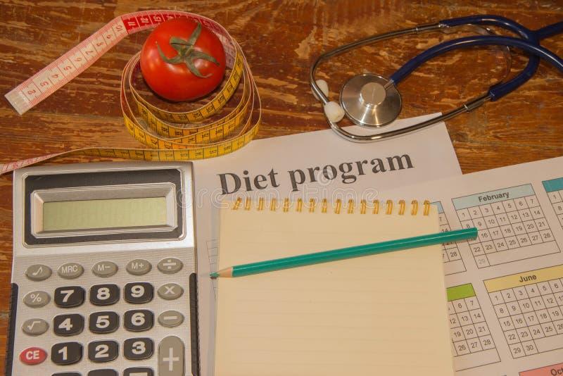 Verdure, pomodoro Misuri il nastro, il calcolatore, il blocco note ed il pomodoro fresco nei precedenti Dieta sana di stile di vi immagine stock libera da diritti