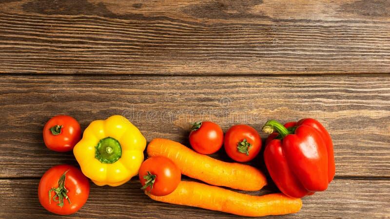 Verdure rosse fresche pomodoro, carote, fondo di legno dei peperoni dolci Concetto di nutrizione e di vegetarianismo sani fotografia stock