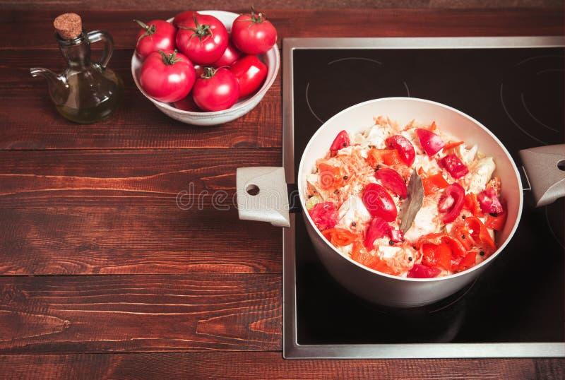 Verdure stufate, pomodori, carote, cavolo, peperoni in una casseruola su una cucina elettrica e una tavola di legno immagine stock