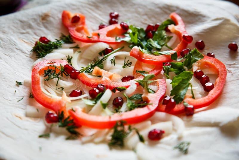 Verdure su un dolce sottile in un piatto Pepe, cipolle, melograno, tortiglia per carne arrostita fotografia stock