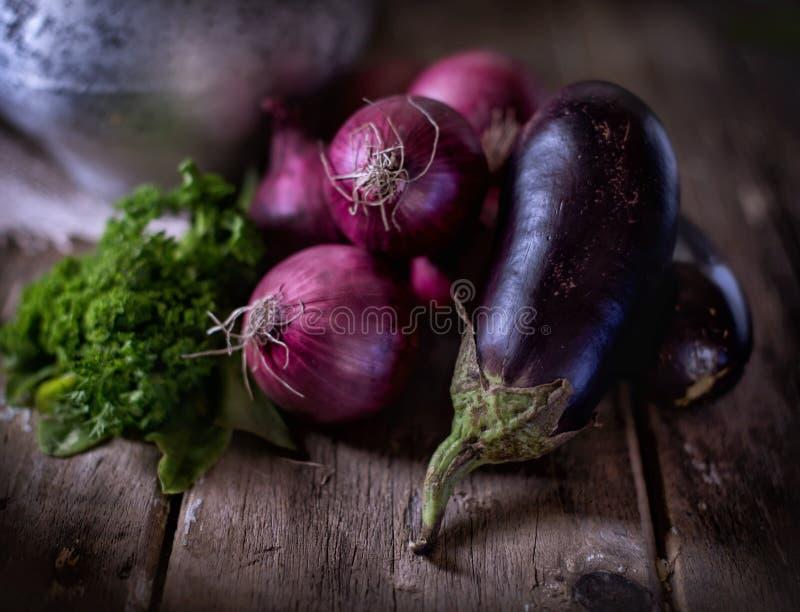 Verdure su una tavola di legno, sulle melanzane, sulle cipolle e sull'insalata immagine stock