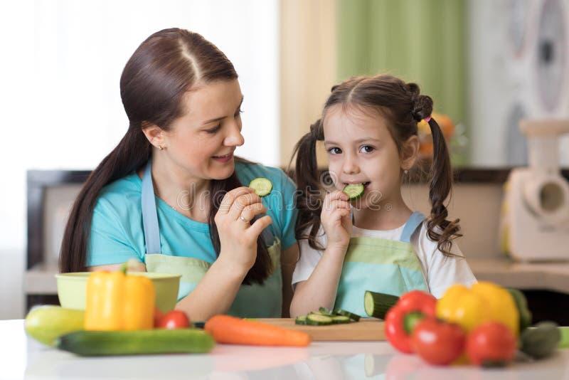 Verdure sveglie dell'assaggio del bambino come prepara un pasto con la loro madre nella cucina immagine stock