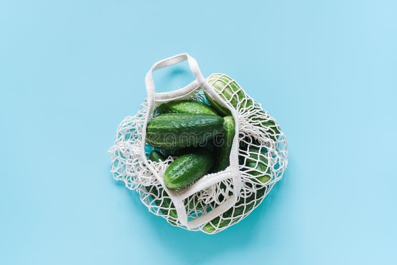 Verdure verdi fresche dei cetrioli nella borsa eco--frendly di compera riutilizzabile della maglia su fondo blu Concetto nessuno  fotografie stock