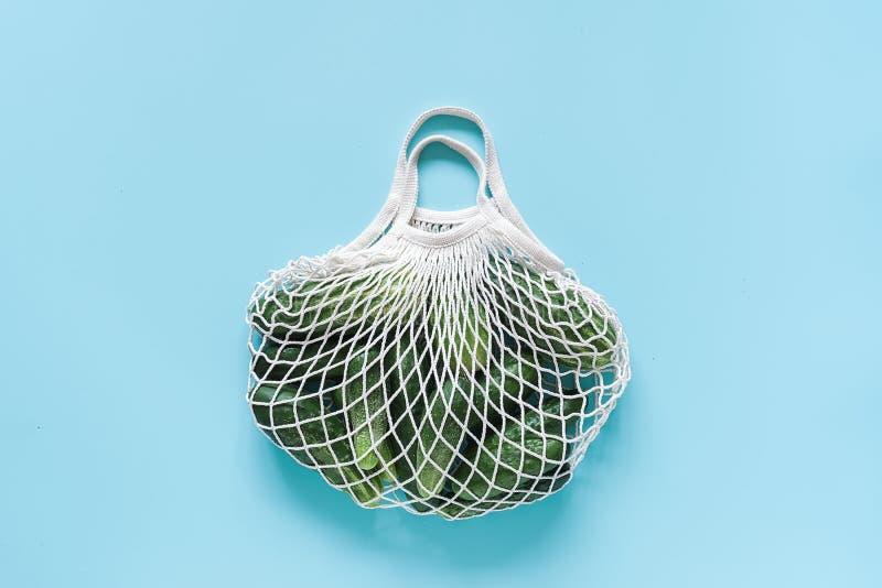Verdure verdi fresche dei cetrioli nella borsa eco--frendly di compera riutilizzabile della maglia su fondo blu Concetto nessuno  fotografia stock