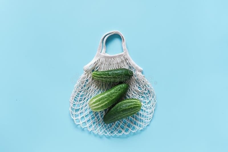 Verdure verdi fresche dei cetrioli sulla borsa eco--frendly di compera riutilizzabile della maglia su fondo blu Concetto nessuno  fotografia stock