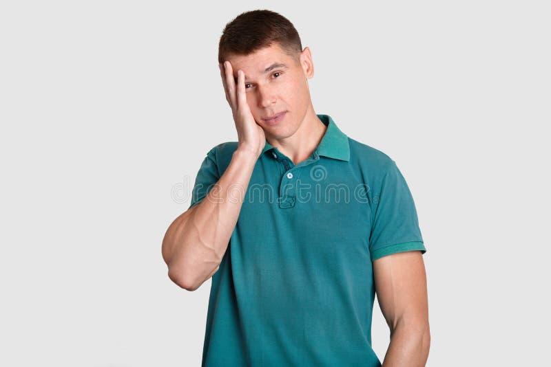 Verdutzter europäischer Mann hält Hand auf Kopf, betrachtet mit frustriertem Ausdruck Kamera, hat etwas Probleme, sich fühlt trau lizenzfreie stockbilder