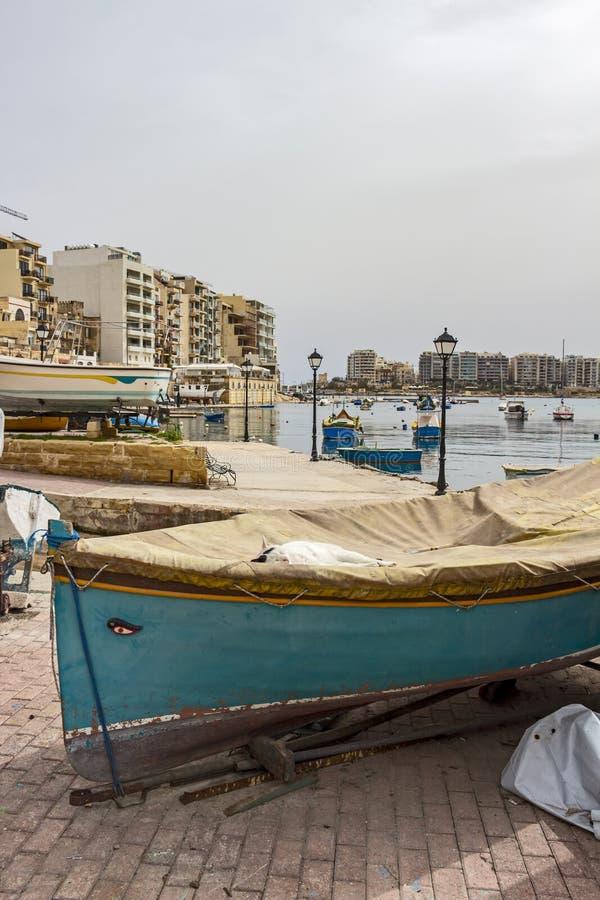 Verdwaalde witte kat met zwarte vlekken op hoofdslaap op een behandelde boot bij Spinola-Baai, St Julian ` s, Malta royalty-vrije stock afbeelding