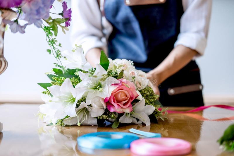 Vereinbarend bekleiden künstliche Blumen Dekoration zu Hause, die Floristenarbeit der jungen Frau, die organisierende diy künstli stockfotografie