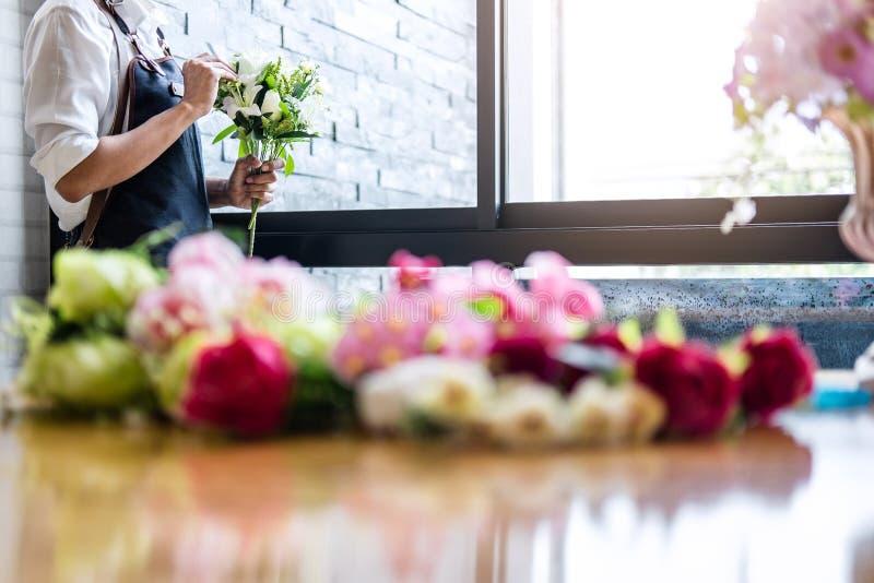 Vereinbarend bekleiden k?nstliche Blumen Dekoration zu Hause, die Floristenarbeit der jungen Frau, die organisierende diy k?nstli lizenzfreie stockfotografie