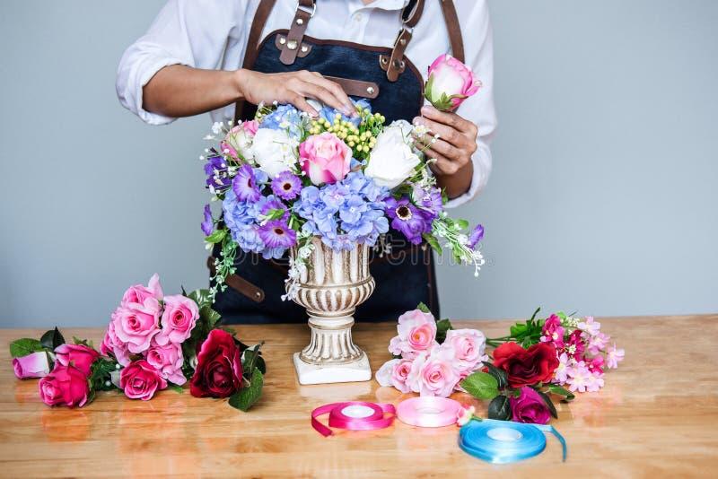 Vereinbarend bekleiden k?nstliche Blumen Dekoration zu Hause, die Floristenarbeit der jungen Frau, die organisierende diy k?nstli lizenzfreie stockfotos